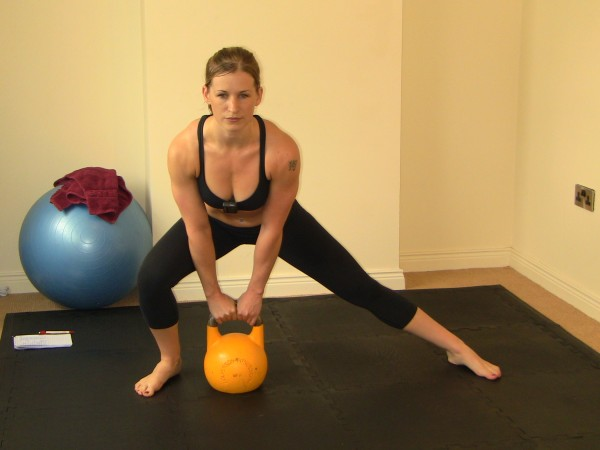 Woman (Marianne Kane) doing Lateral Lunge with Kettlebell during Men's Health Spartacus Workout